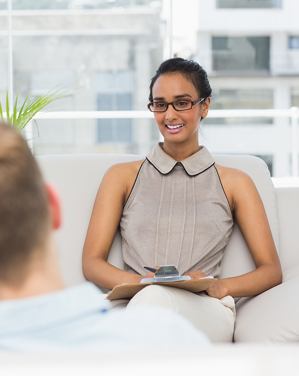 Therapist smiling at couple on the couch in therapists office